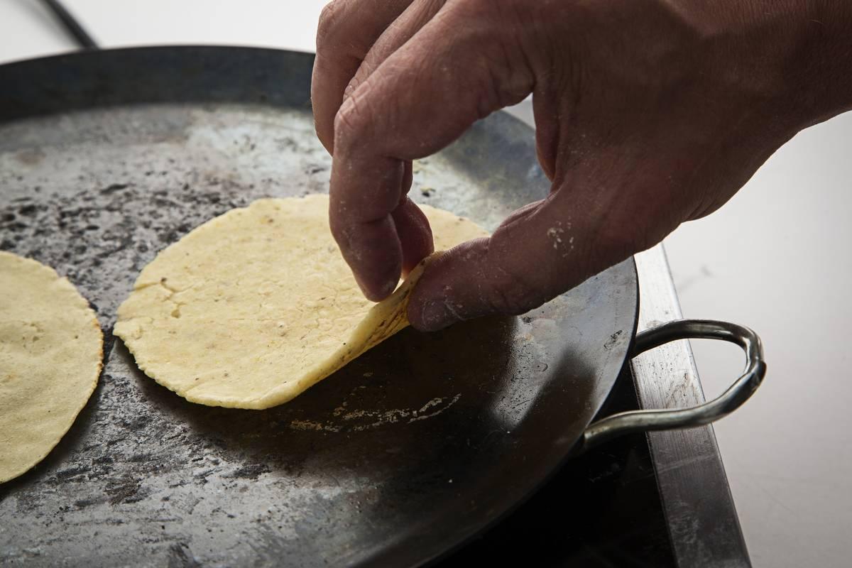 A man lifts a corn tortilla from a pan.
