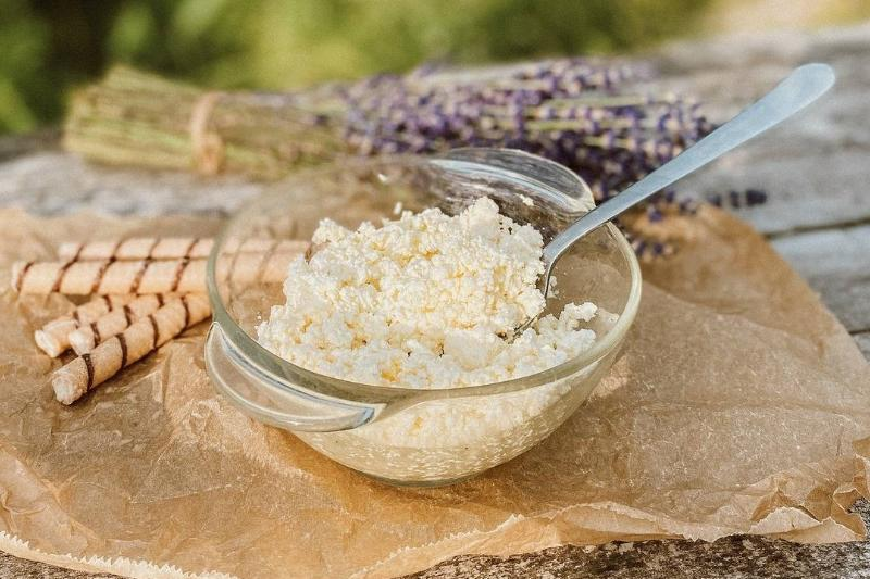 A bowl of cottage cheese sits outside on a wooden table.