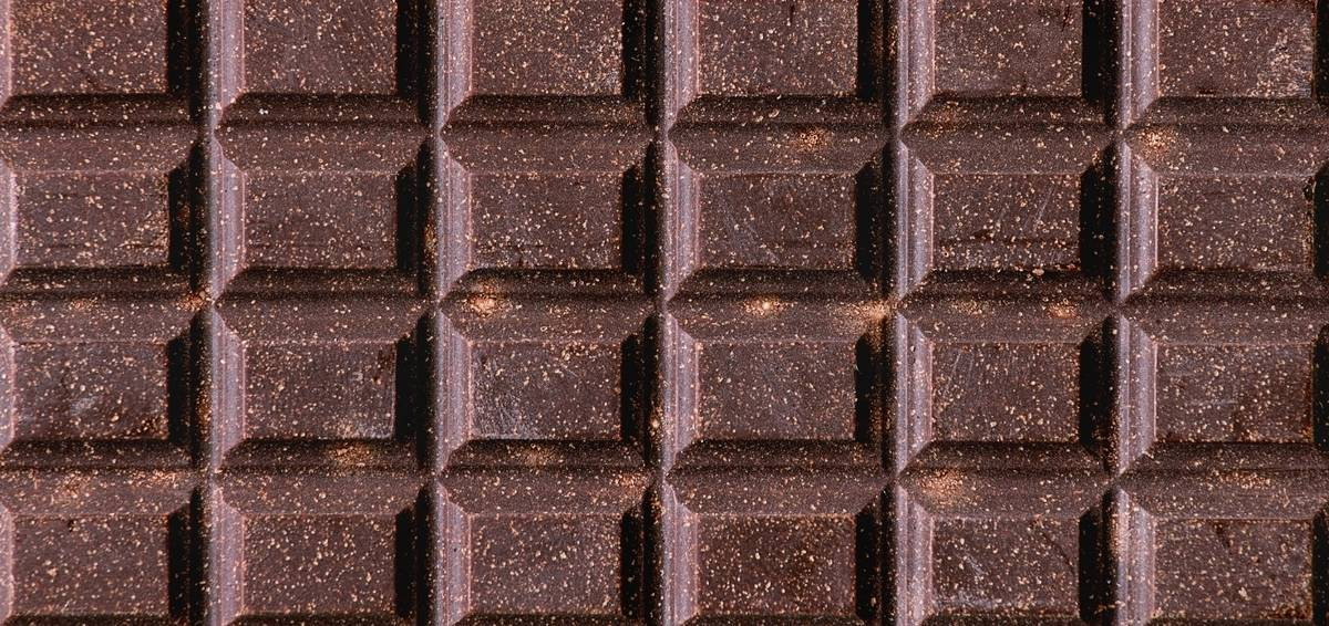 A close-up picture shows squares of a dark chocolate bar.