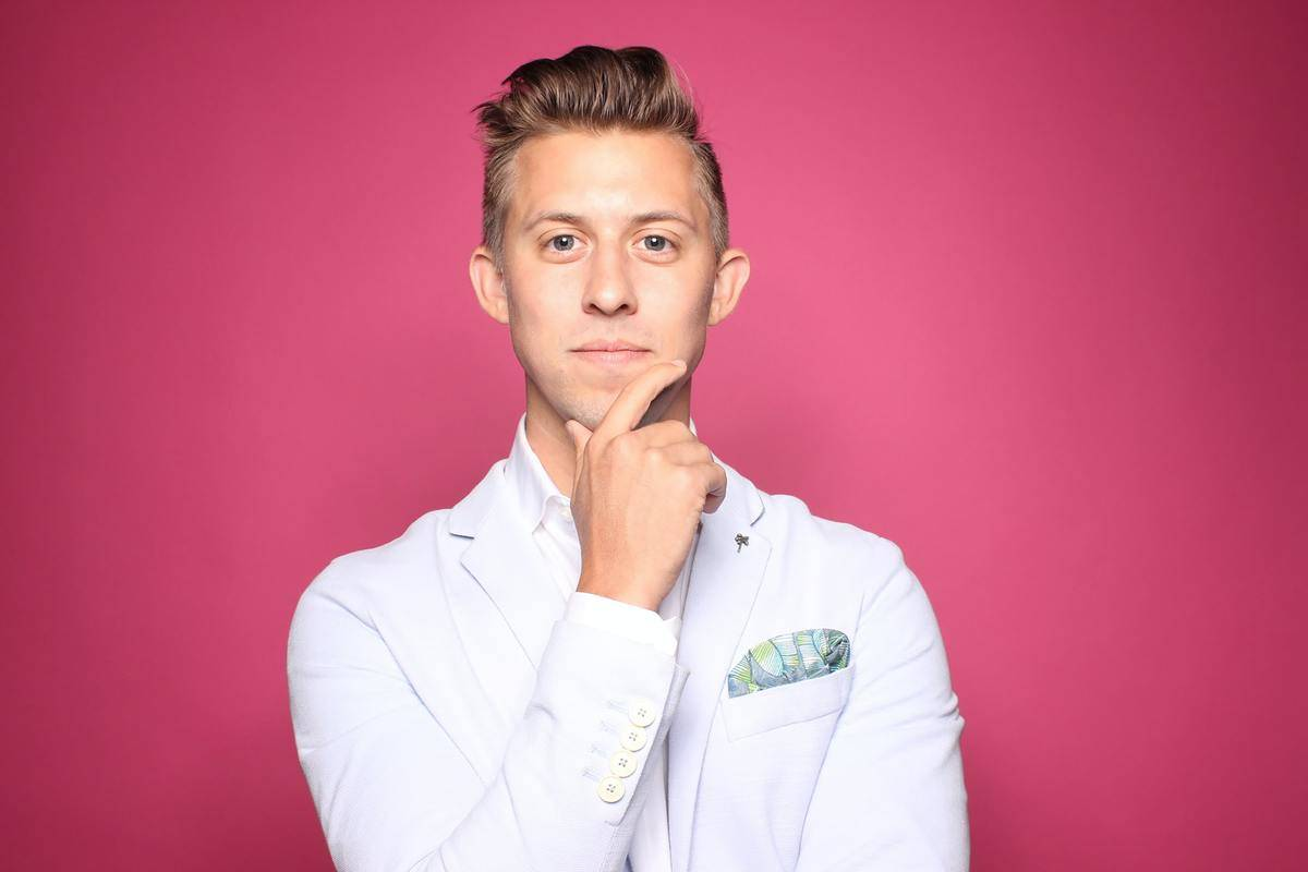 a doctor posing for a photo with a pink background