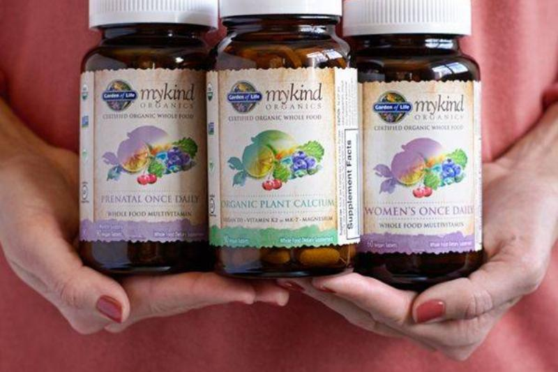 A woman holds three varieties of Garden of Life vitamins.