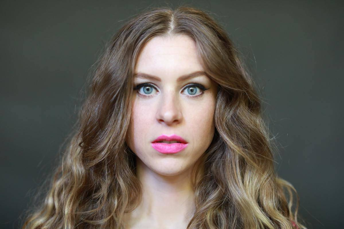 a girl with long hair and bright pink lipstick