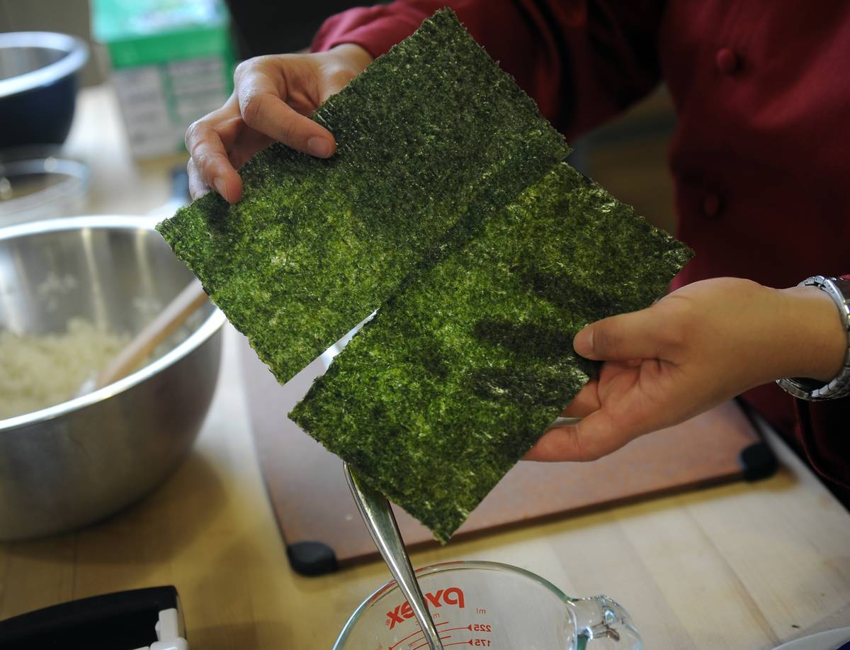 A chef holds two roasted seaweed sheets.