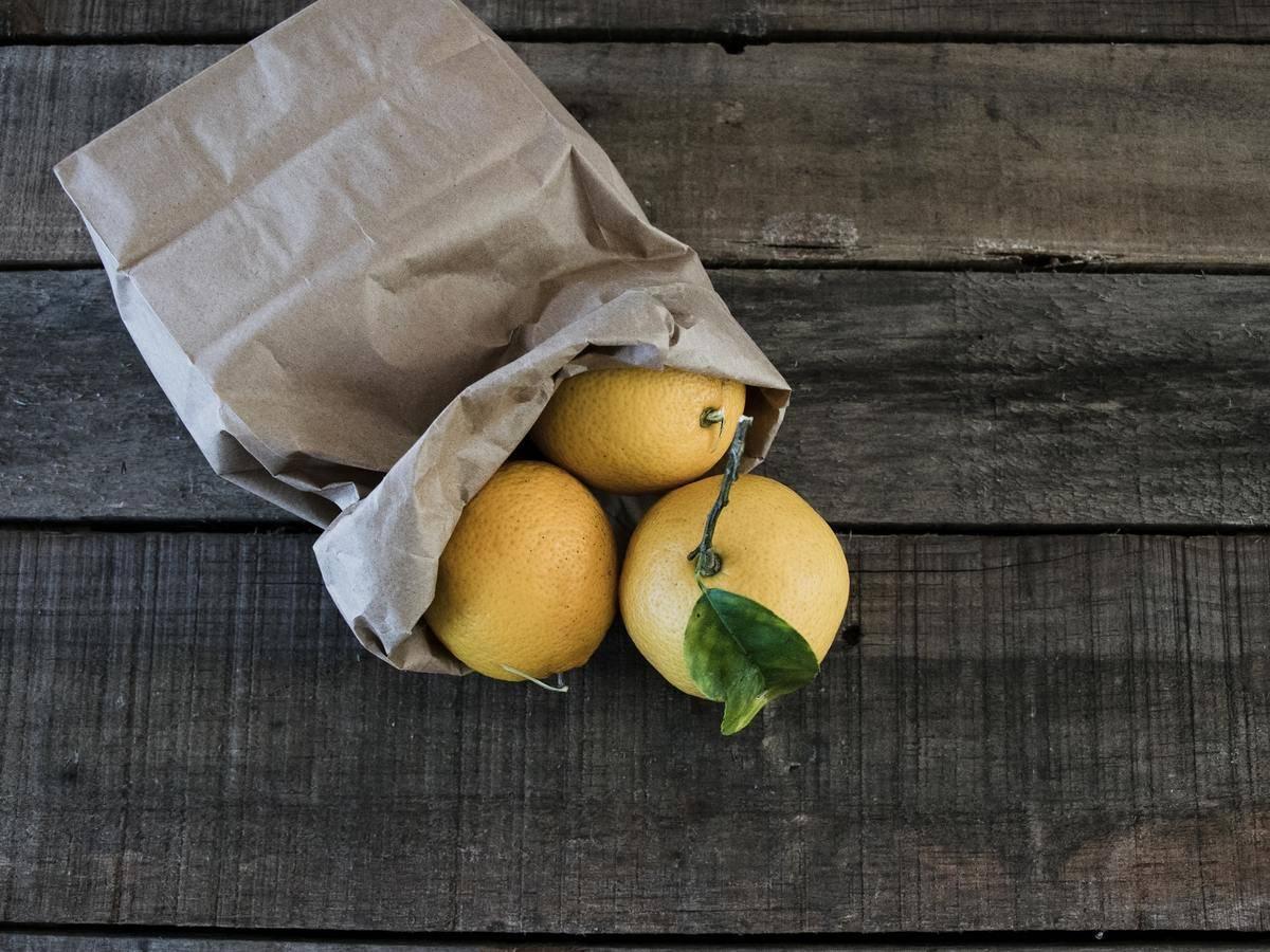 Three lemons pour out of a paper bag.