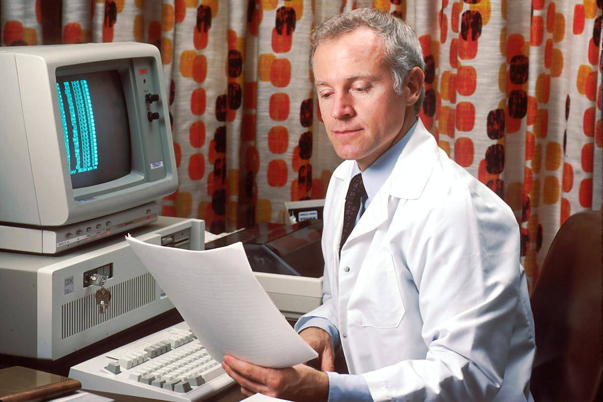 doctor with retro computer looking at paperwork