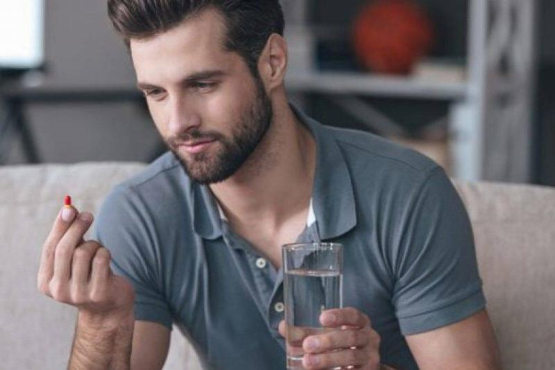 A man looks at a pill while holding a glass of water.