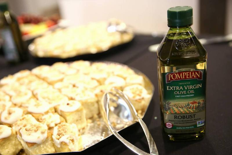 A bottle of olive oil is seen next to Mediterranean food.