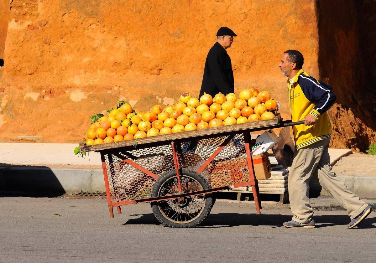 a man pushing an orange cart