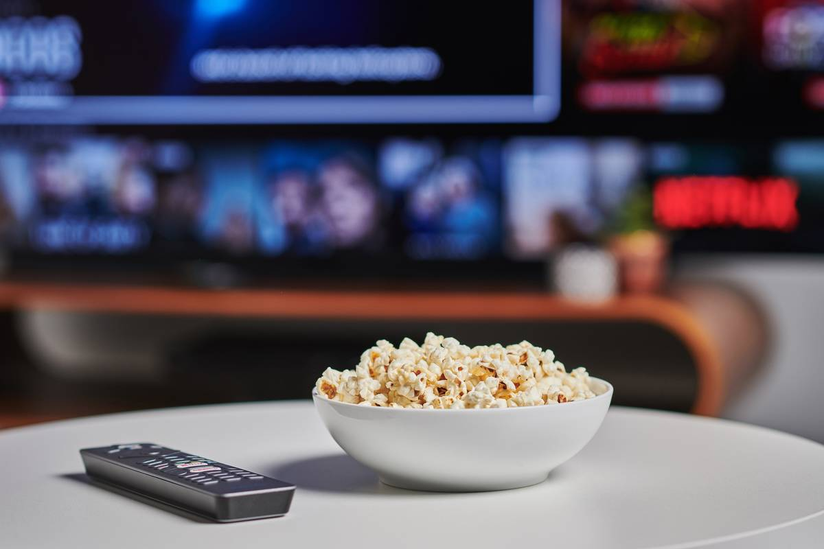 A bowl of popcorn is seen next to a TV remote in front of the TV.