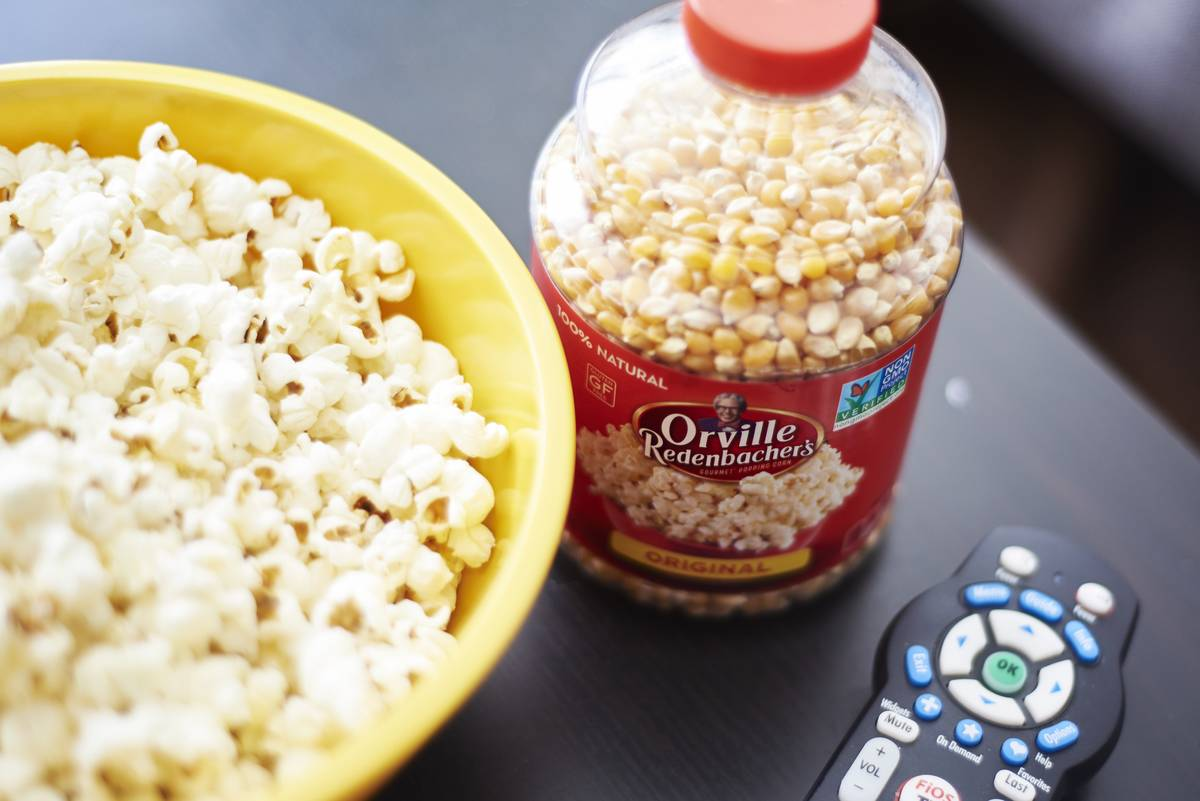 Popcorn kernels sit next to a TV remote and a bowl of unflavored popcorn.