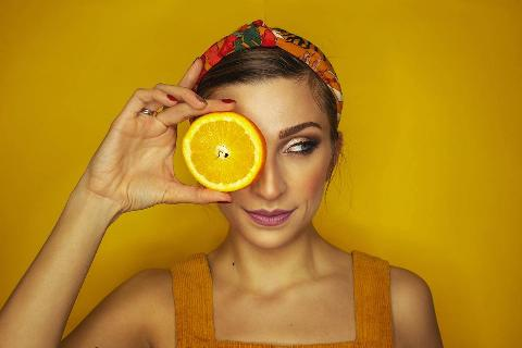woman holding orange slice in front of her eye