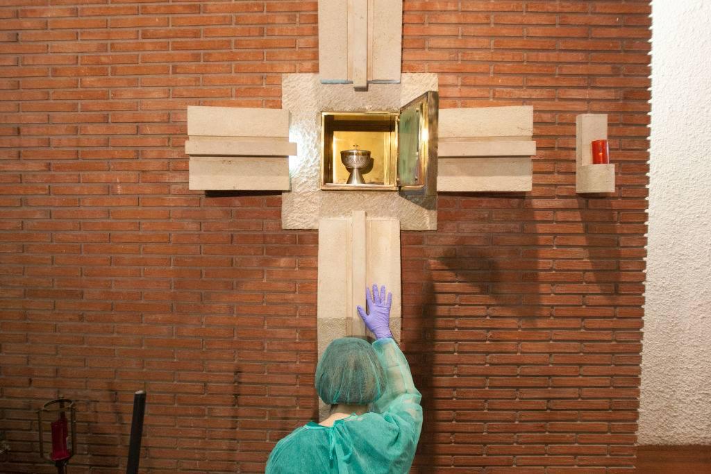 A nurse kneels before the tabernacle