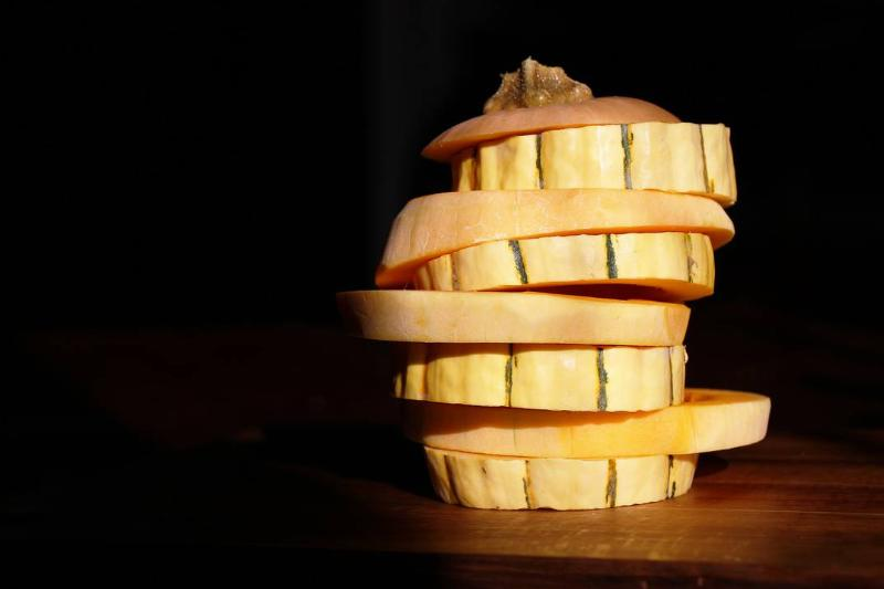 A stack of butternut and delicata squash rings is in a dark room.