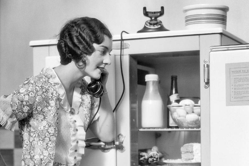 A woman smiles and looks into her refrigerator/icebox while talking on the phone.