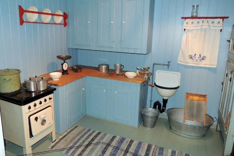 A blue kitchen from 1945 features wooden countertops, plates on display, and embroidered curtains.