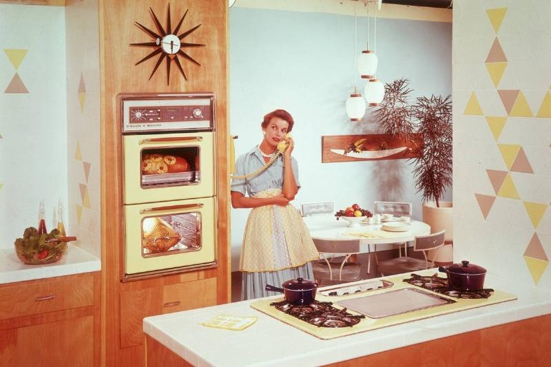 A housewife speaks on the phone in a kitchen.
