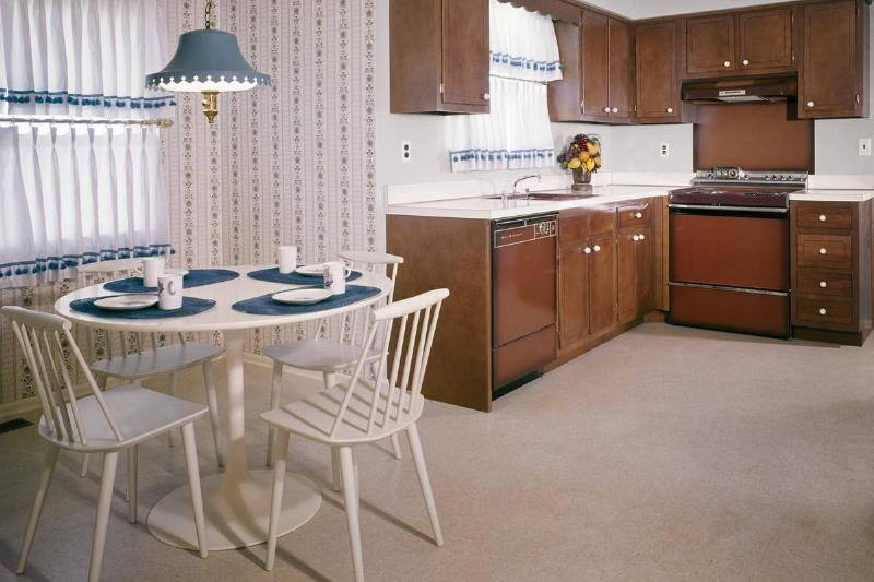 In a 1960s dining room/kitchen area, the wall is decorated with patterned wallpaper.