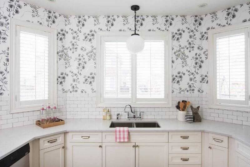 A modern kitchen has an accent wall with floral wallpaper.