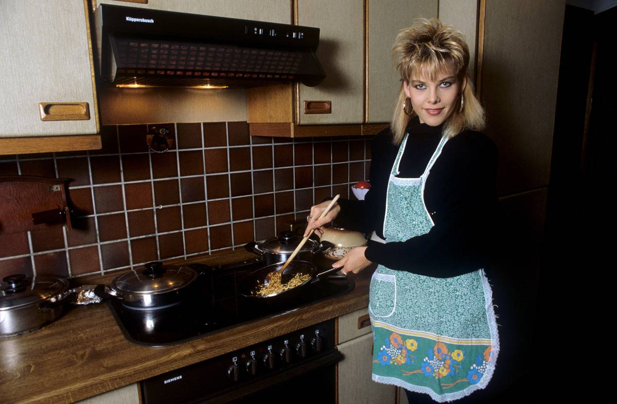In 1987, a woman cooks in a kitchen that has a backsplash of brown tiles.