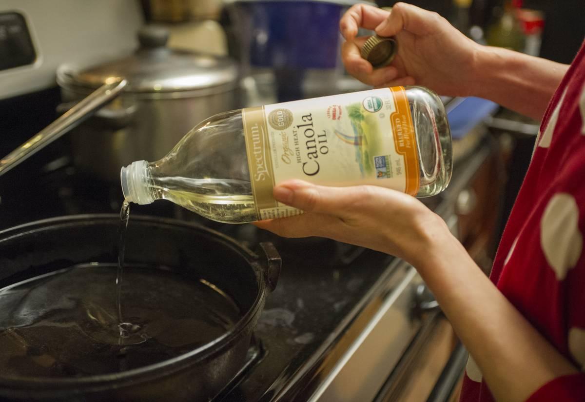 A woman pours canola oil into a pan.