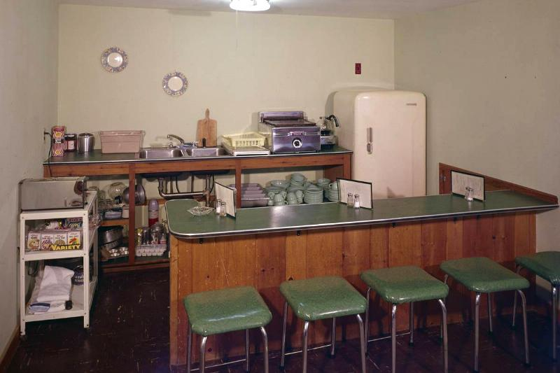 A 1960s kitchen with a bar has green laminate on the countertop.