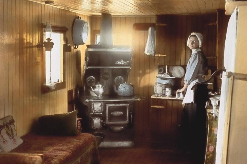In this colorized photo from 1915, a woman stands in her small kitchen.
