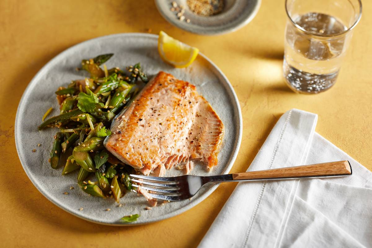 A dinner plate includes salmon with a side salad.
