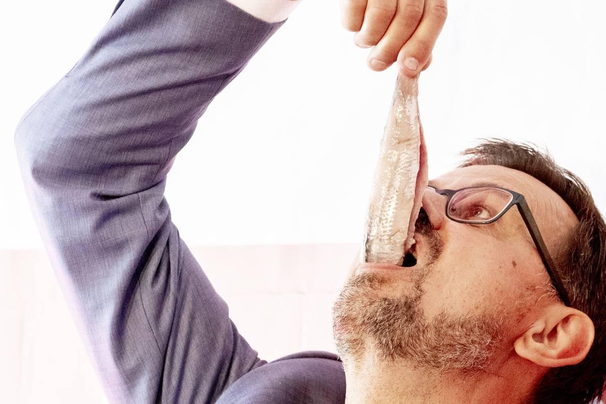 A man eats a herring whole.