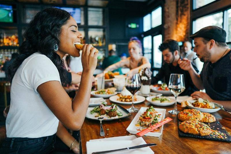 A woman enjoys pizza while eating out with friends.