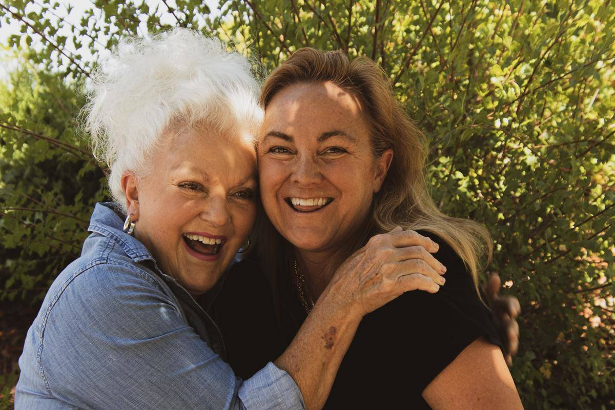 Two elderly women embrace each other and smile.