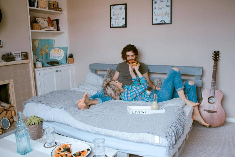 woman feeding pizza to man in bed