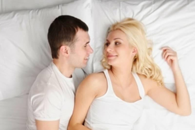 man and woman spooning a little far apart in loose spoon position