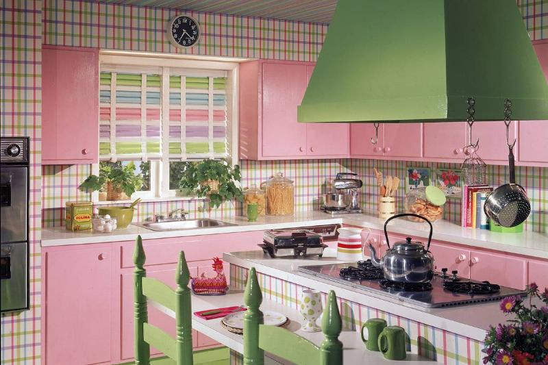 A model 1970s kitchen includes green and pink plaid wallpaper with pink cabinets, and green chairs.