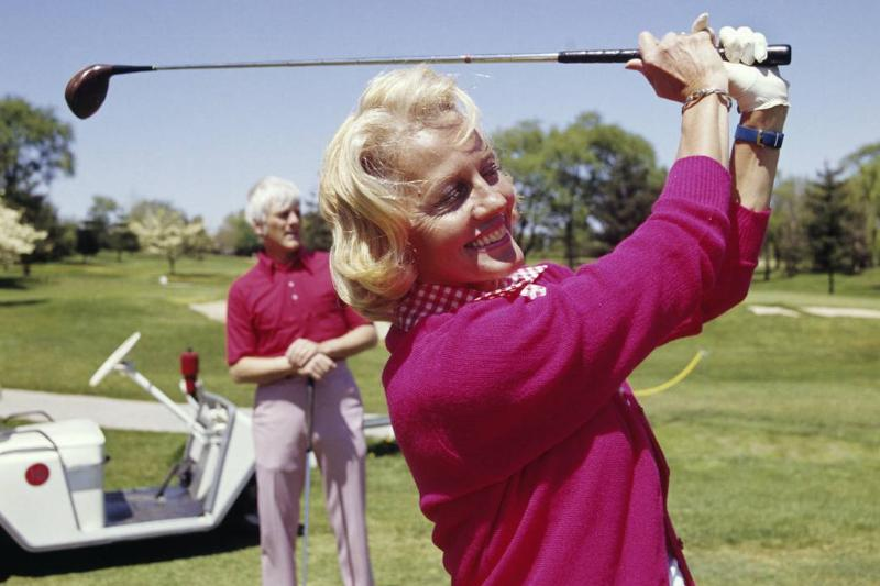 A woman smiles while playing golf.
