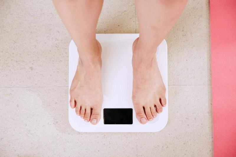 A woman stands on a scale to check her weight.
