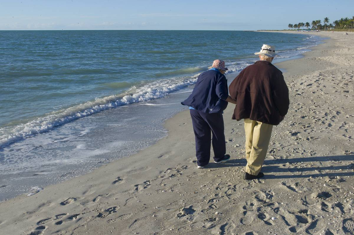 An elderly couple walks along a Florida beach together.
