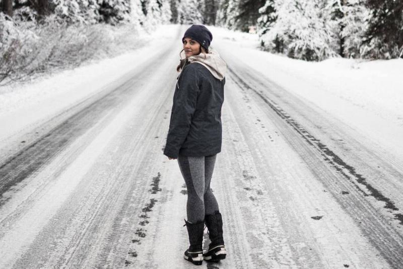 A woman turns around while walking down a snowy road.