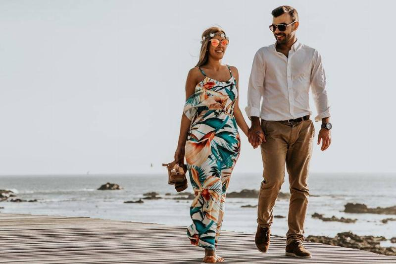 A couple walks together on a boardwalk.