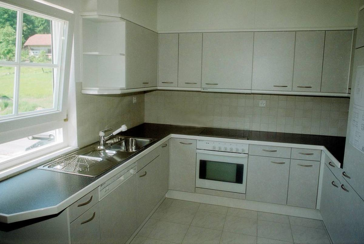 This 1996 kitchen has white cabinets, oven, and refrigerator.