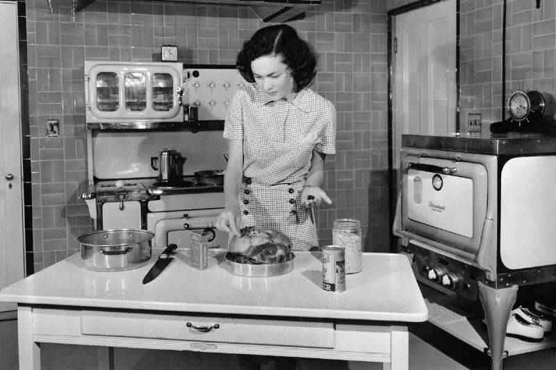 A woman cooks in her kitchen in 1938.