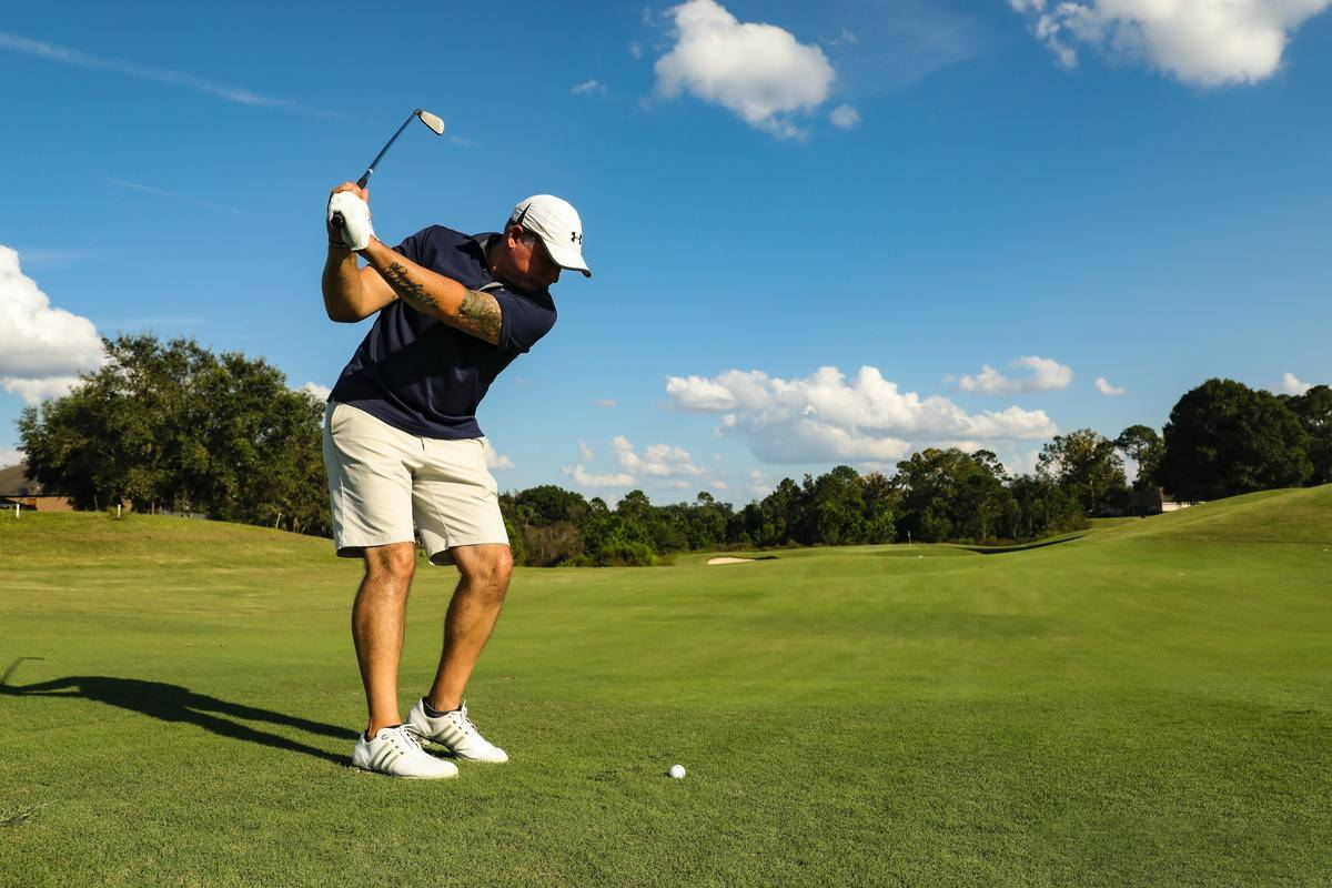 a man swinging a club to hit a golf ball at a golf course