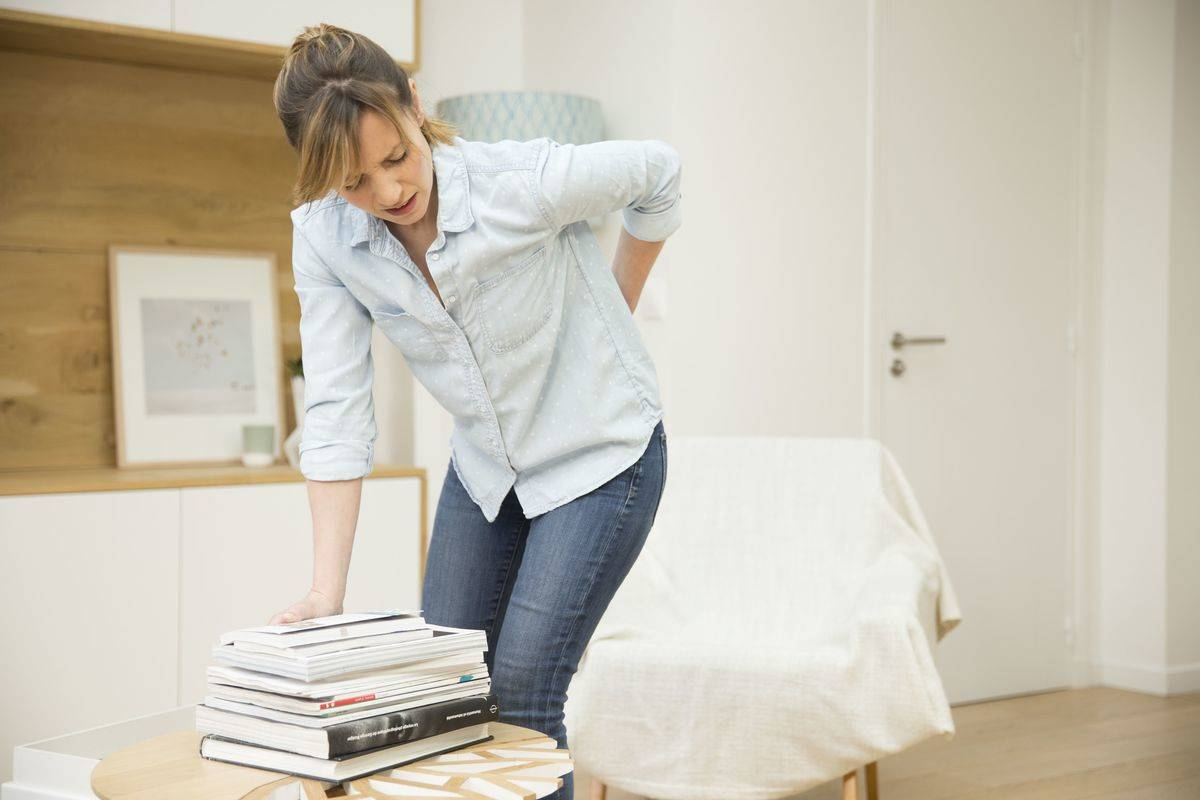 A woman experiences back pain while leaning down to pick up books.
