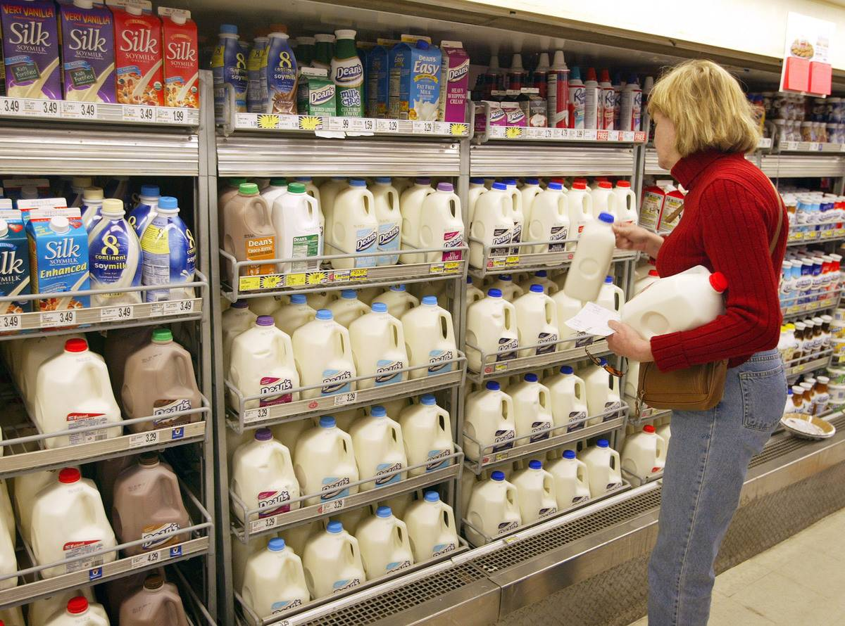 A woman buys two gallons of milk from the grocery store.