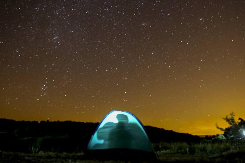 People camp in a tent underneath a starry sky.