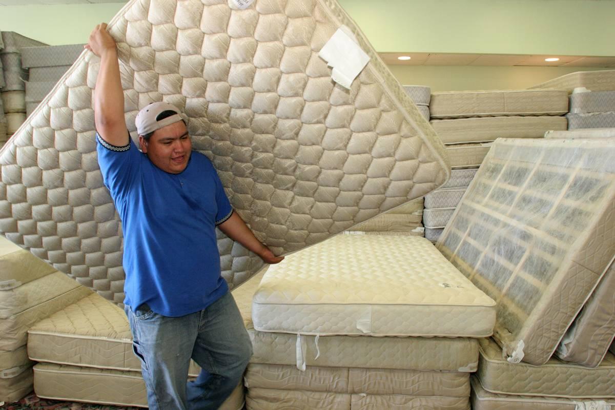 A man carries a mattress out of a store.