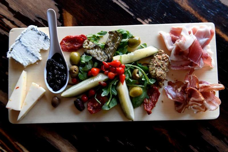a charcuterie board with meat, cheese, salad, olives, pickles, and berries