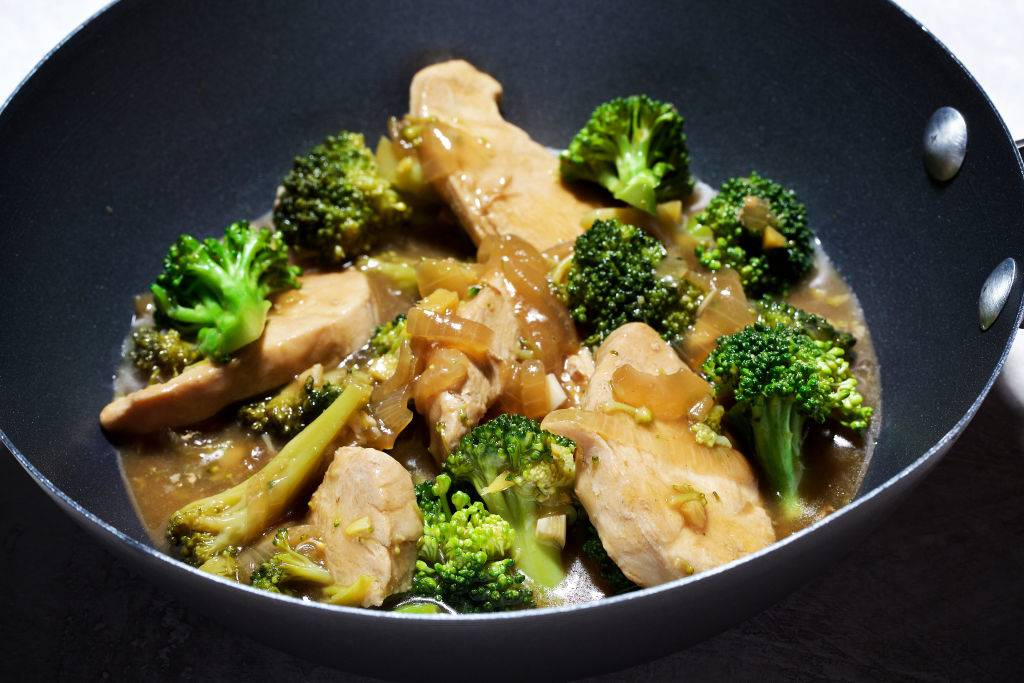 chicken stir fry with onions and broccoli in a wok