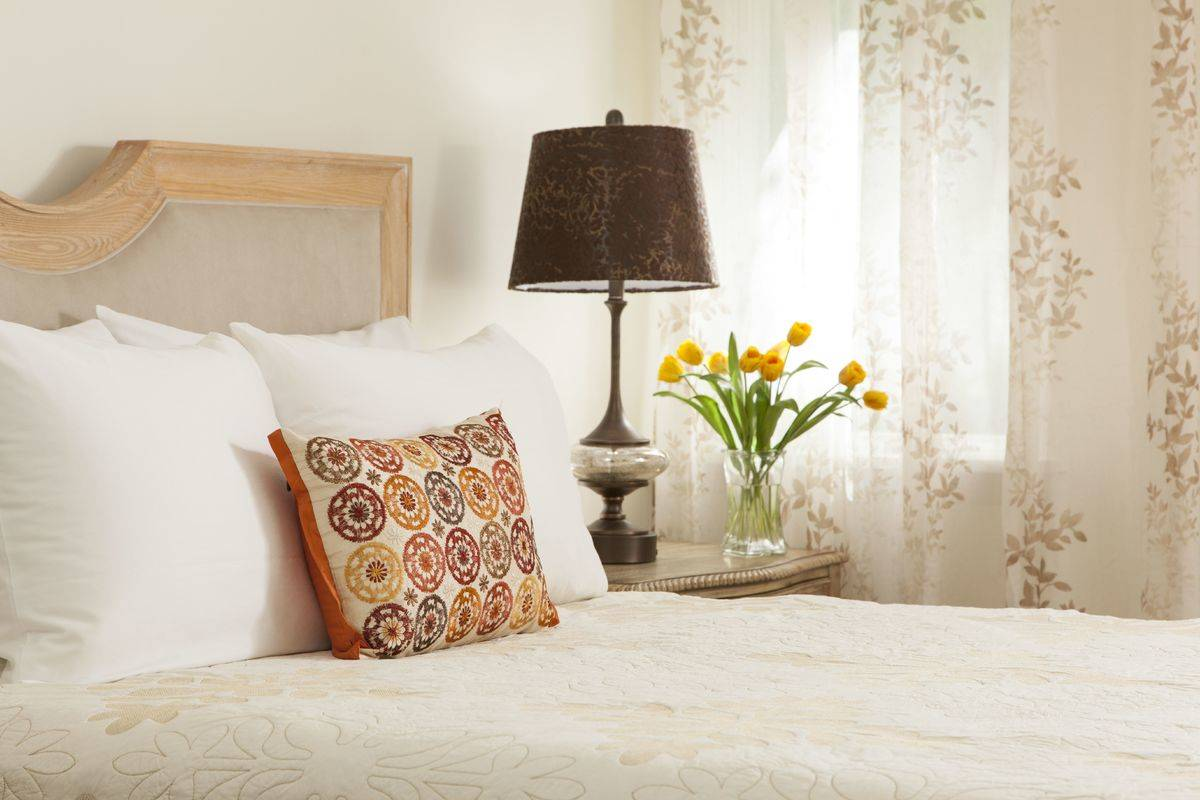A bedroom is decorate to look and feel cozy.