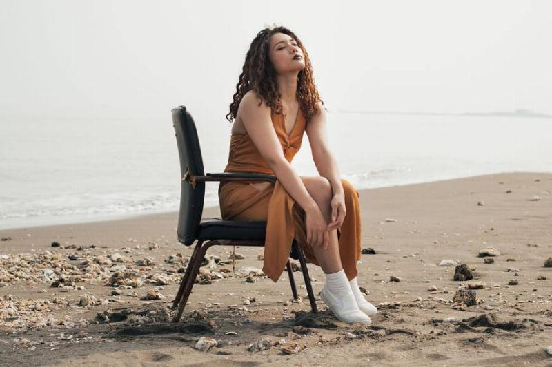 a girl sitting on a chair at the beach