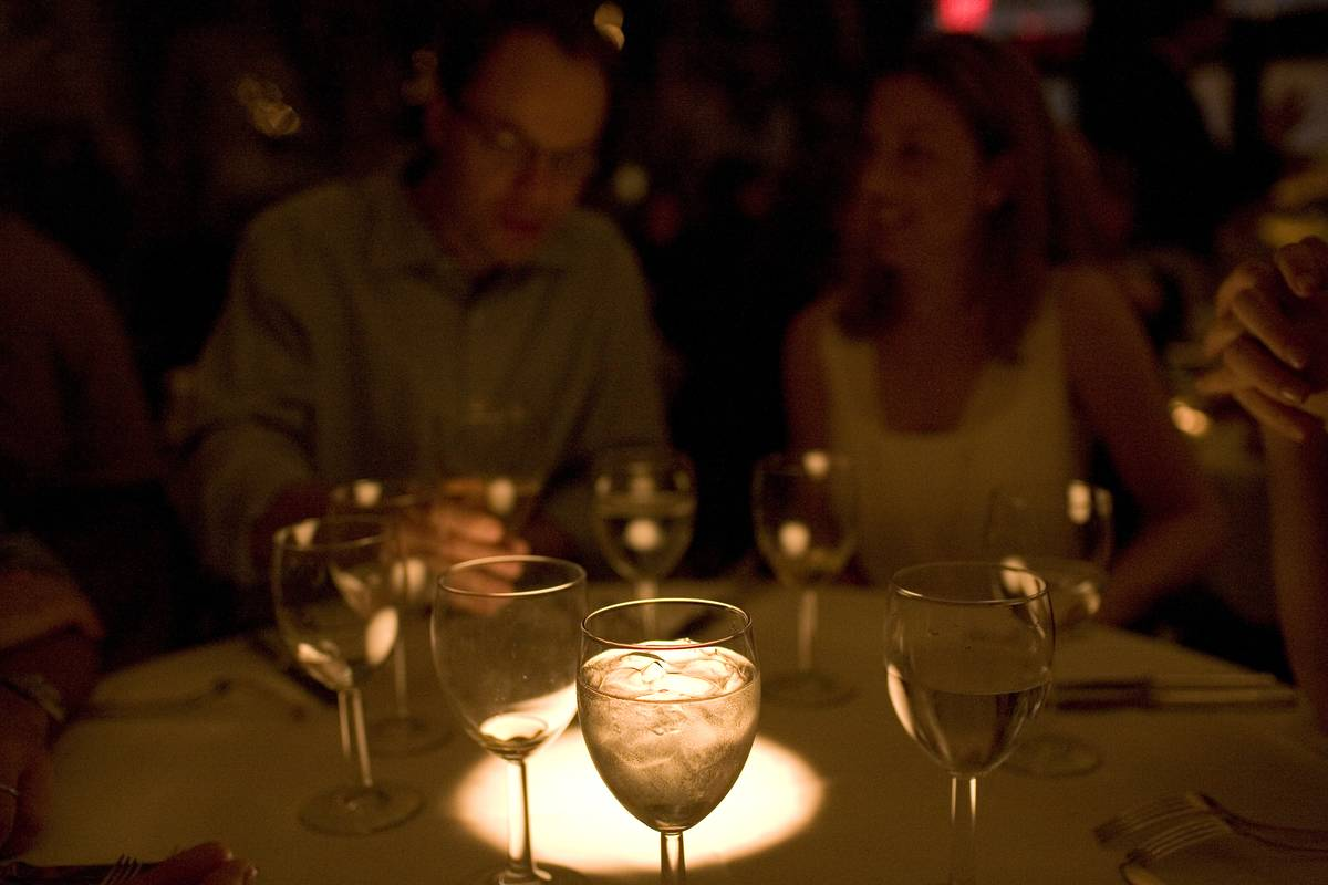 Water and wine glasses are highlighted in a dimly-lit restaurant.